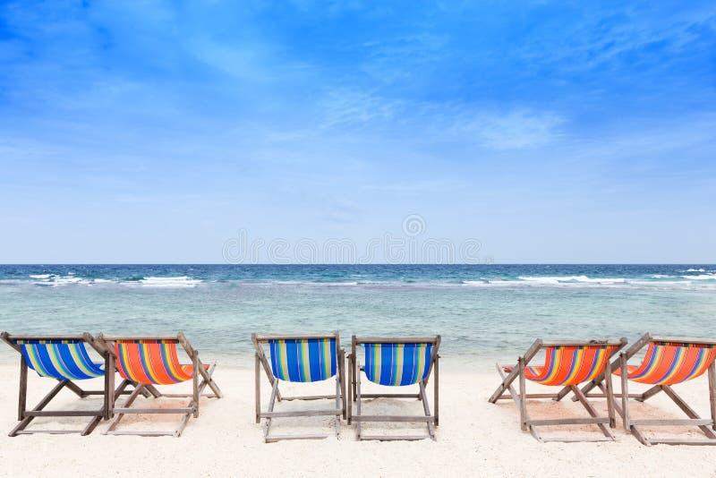 Шезлонги на пляже с белым песком с пасмурным голубым небом стоковое изображение rf