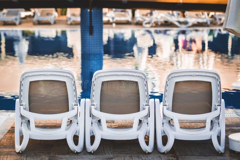 Шезлонги около бассейна стоковая фотография