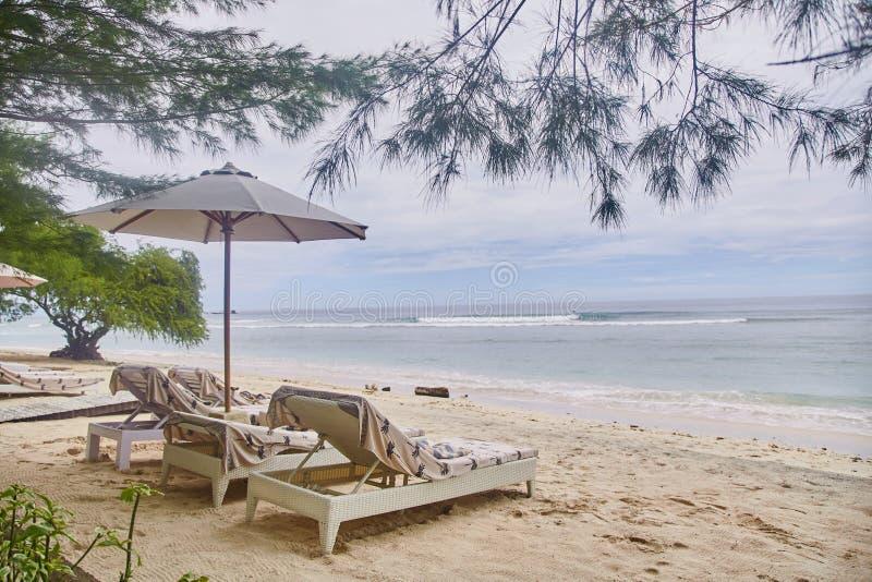 Шезлонги с зонтиками на пляже Бали стоковое изображение