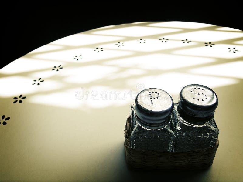 Шейкеры соли & перца, таблица кафа в солнечном свете стоковые фотографии rf