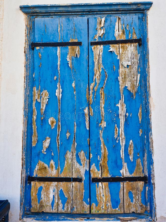 Шелушиться и бляшечная голубая краска на деревянных шторках окна стоковая фотография