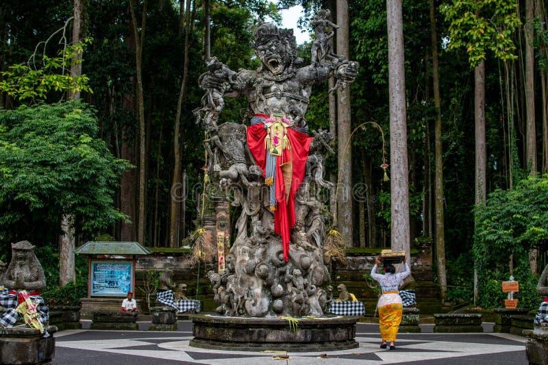 Шествие красивых балийских женщин в традиционных костюмах - саронг, идя к индусской церемонии около большого памятника демона стоковая фотография