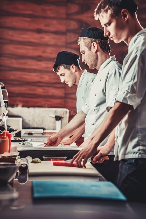 Шеф-повара варят суши в ресторане стоковое фото