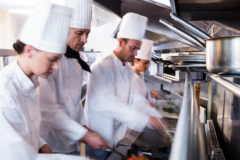 Шеф-повара подготавливая еду в кухне стоковые фотографии rf