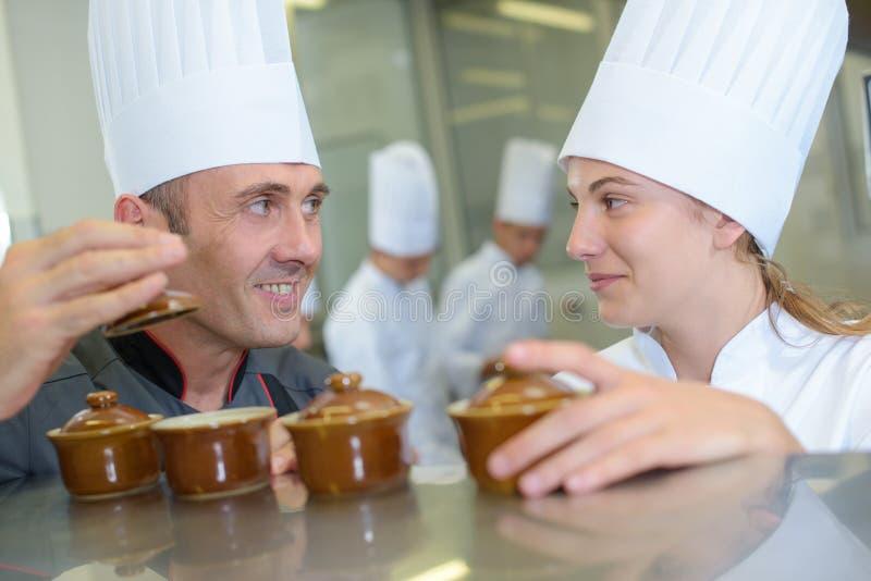 2 шеф-повара усмехаясь и держа баки ramekin стоковые фото