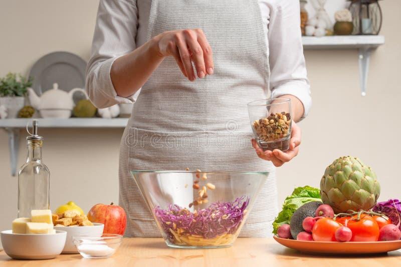 Шеф-повар брызгает салат с гайками, шевелит, в процессе вегетарианского салата с рукой шеф-повара в домашней кухне Свет стоковые фото