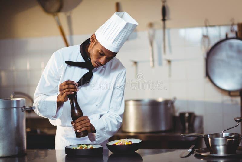 Шеф-повар брызгая перец на еде стоковая фотография