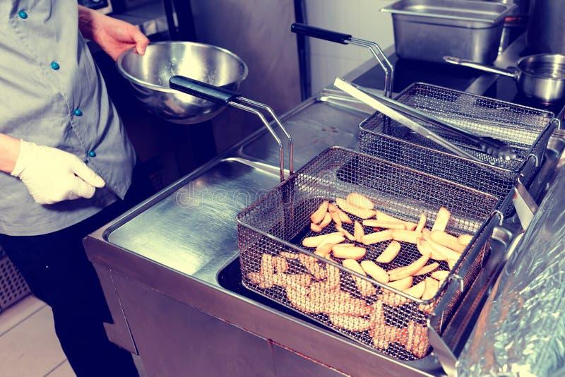 Шеф-повар варит французские тонизированные фраи, стоковые фото