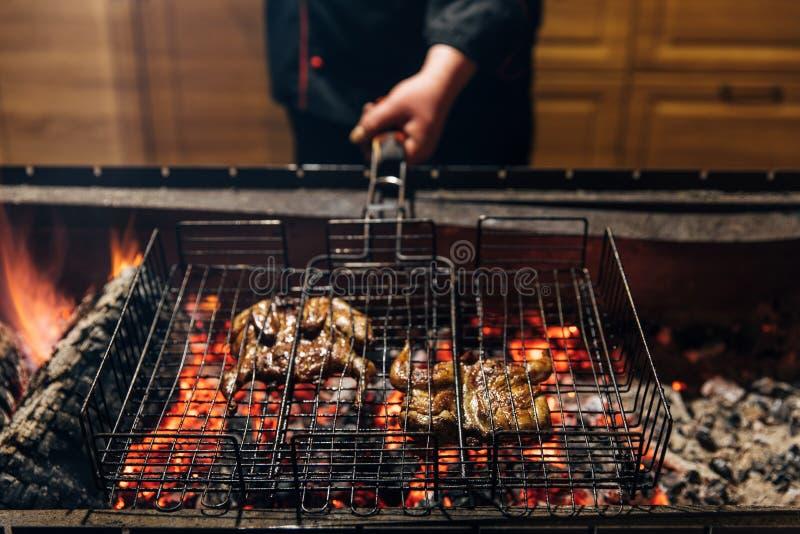 Шеф-повар варя мясо на пламени в баре гриля стоковые фото