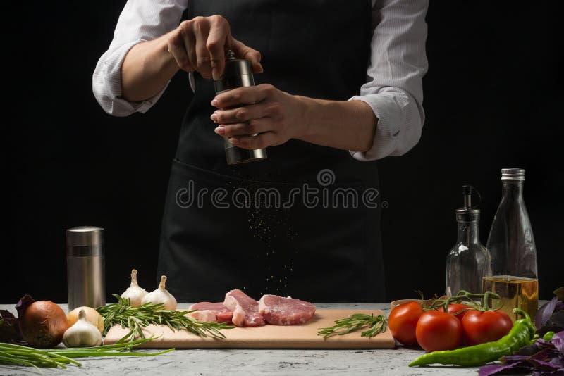 Шеф-повар, варя мясо стейка в кухне, брызгая с черным перцем, на предпосылке овощей, томат, горячий перец, базилик, стоковое изображение