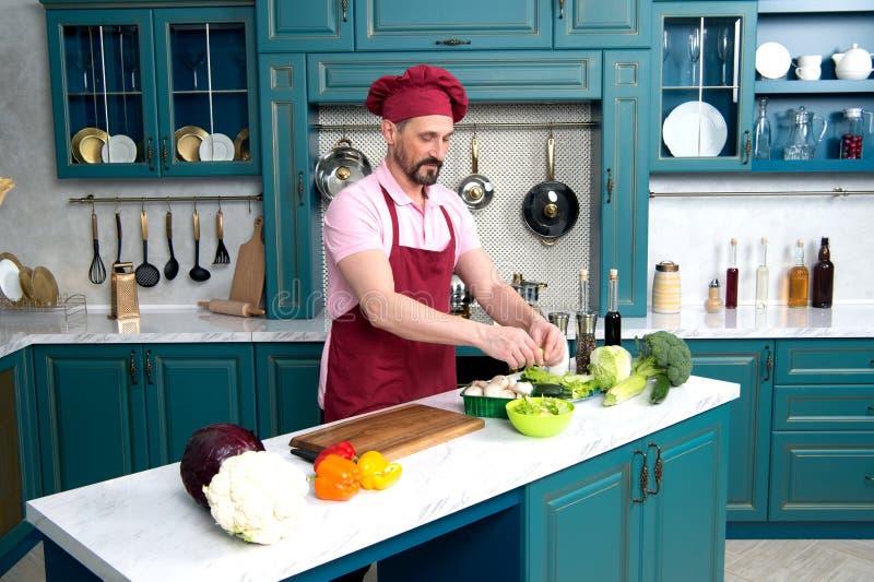 шеф-повар варя попытки кухни тарелки Человек на кухне варя свежий вегетарианский завтрак Гая подготавливает салат с зелеными овощ стоковая фотография rf