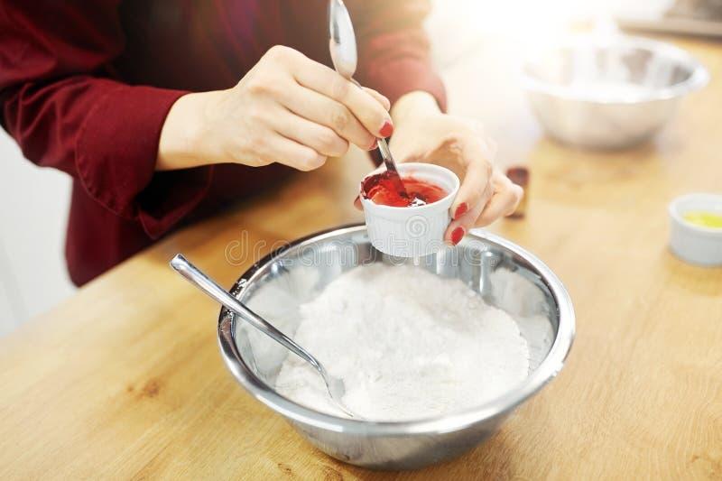 Шеф-повар вручает добавлять цвет еды в шар с мукой стоковые фото