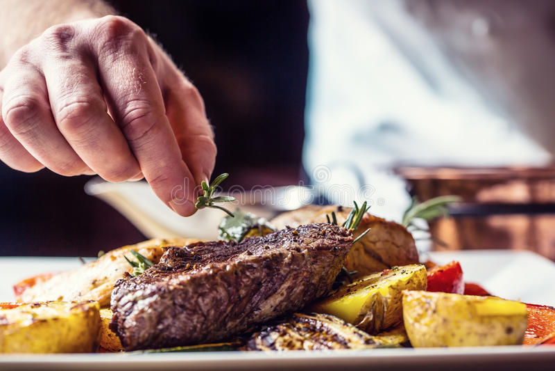 Шеф-повар в кухне гостиницы или ресторана варя только руки Подготовленный стейк говядины с vegetable украшением стоковое фото