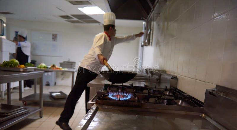 Шеф-повар в кухне гостиницы подготавливает еду с огнем стоковое фото rf