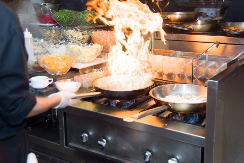Шеф-повар в кухне ресторана на плите при лоток, делая flambe на еде фокус низкого ligth селективный стоковая фотография rf