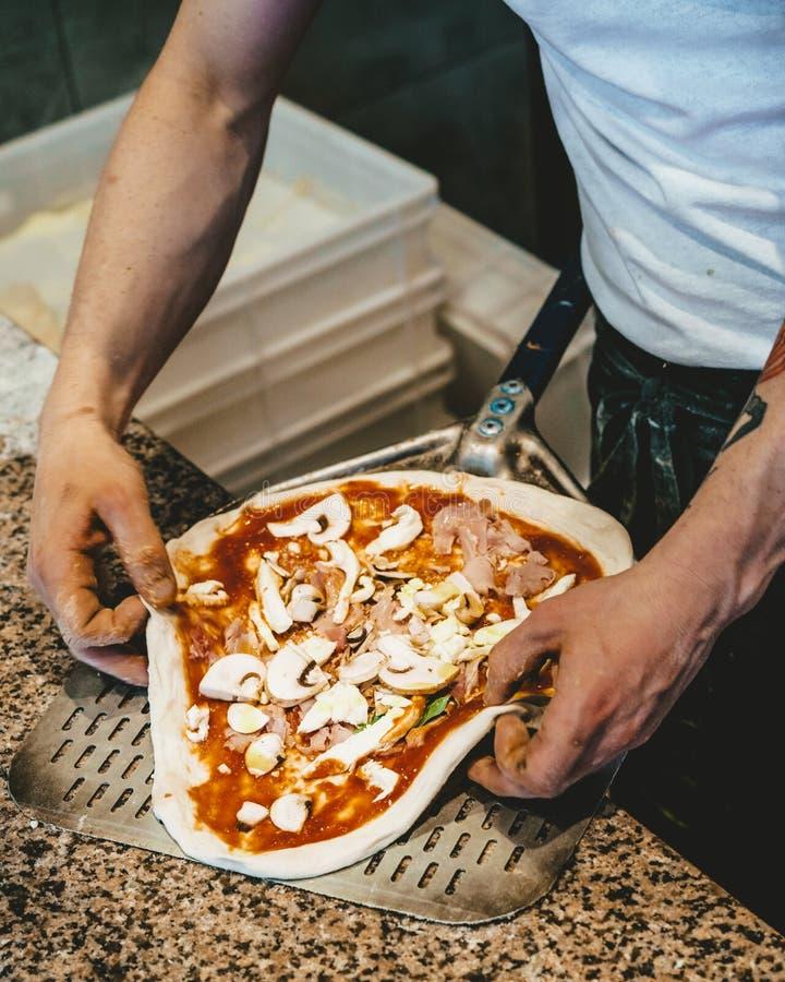 Шеф-повар делая свежую пиццу вручную стоковые изображения rf