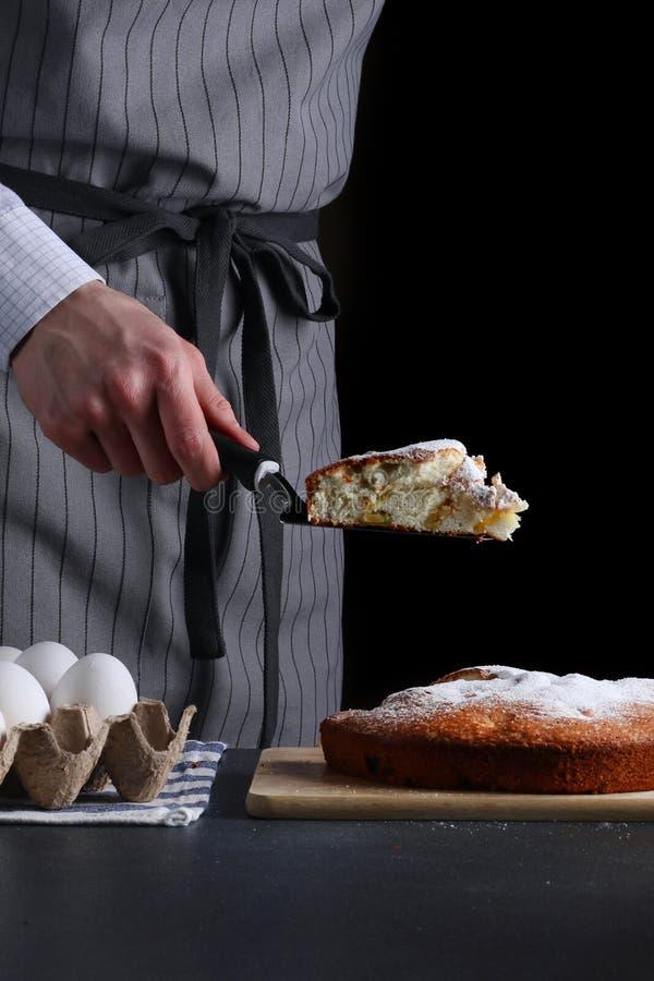 Шеф-повар держа кусок пирога на черной предпосылке делать и подача пирога стоковая фотография