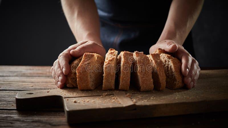 Шеф-повар держа хлеб перед деревянной разделочной доской стоковое фото rf