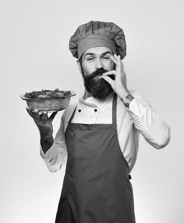 Шеф-повар держит шар при сотейник картошки показывая супер вкусный знак Кашевар с счастливой стороной в бургундских испеченных вл стоковое изображение