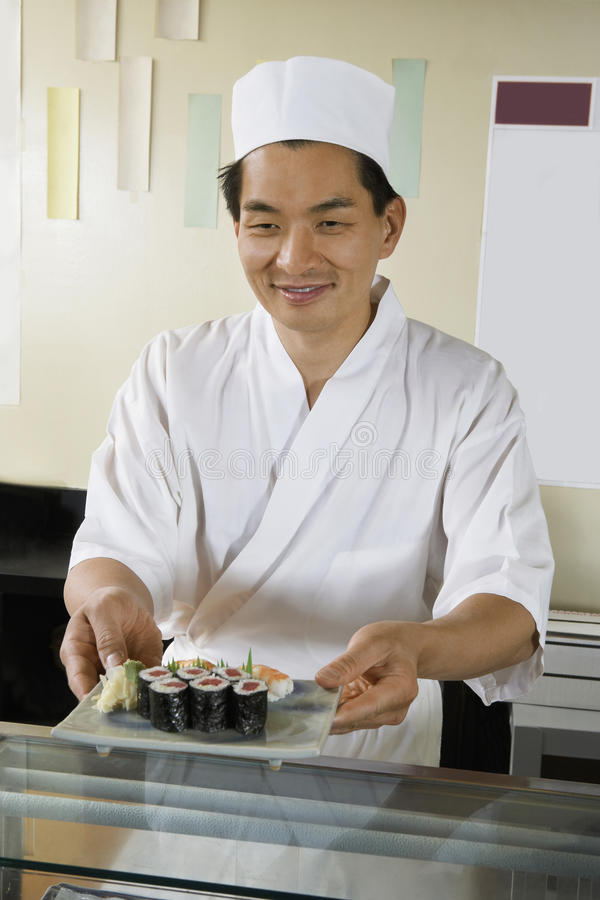Шеф-повар держа плиту суш в ресторане стоковое фото