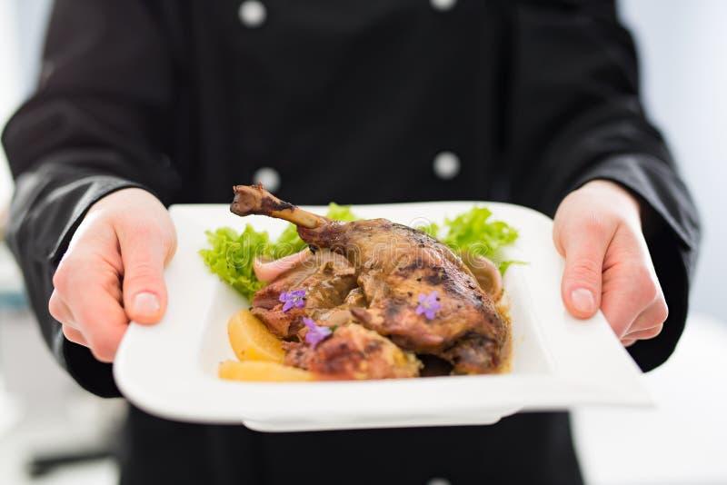 Шеф-повар держит совершенный сделанный обедающий стоковые фото