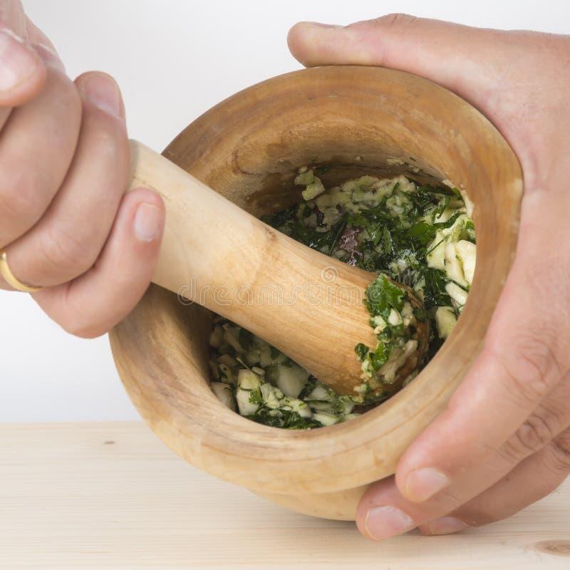 Шеф-повар задавливая чеснок и петрушку с минометом и пестиком в k стоковая фотография