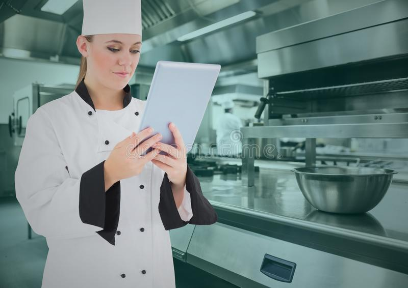 Шеф-повар используя цифровую таблетку в коммерчески кухне стоковая фотография