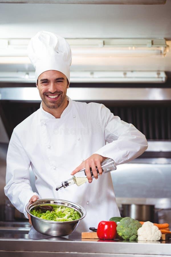 Шеф-повар кладя масло на салат стоковое изображение