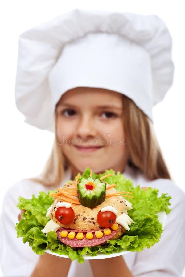 Шеф-повар маленькой девочки держа творческое sandvich стоковые фото