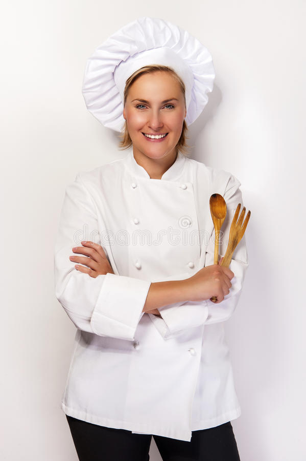 Шеф-повар молодой женщины держа деревянные ложку и вилку стоковое изображение