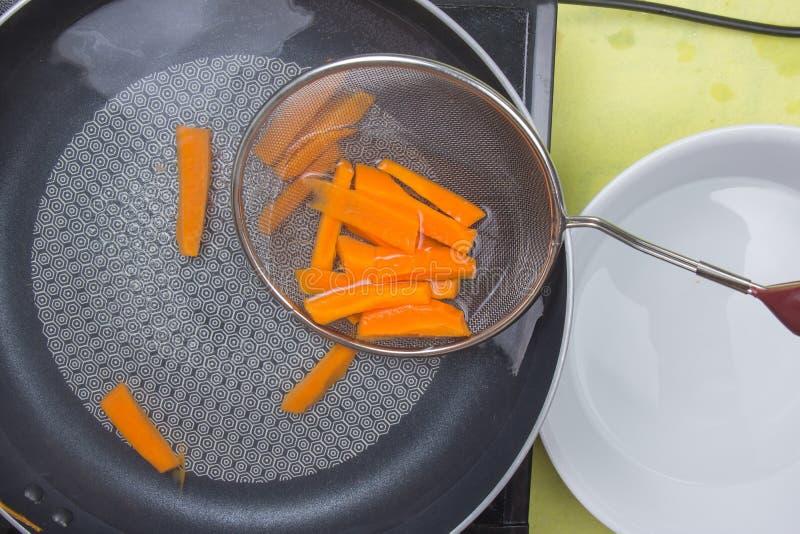 Шеф-повар ошпаривает морковь с горячей водой стоковая фотография rf