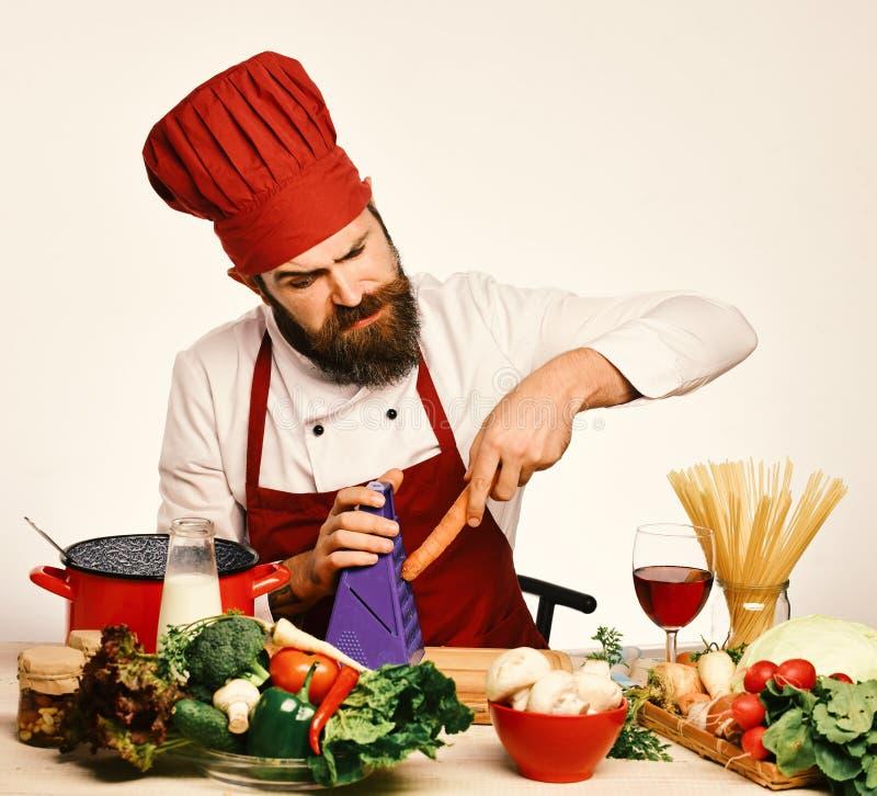 Шеф-повар подготавливает еду Концепция варочного процесса Кашевар с серьезной стороной в форме сидит кухонным столом стоковые фотографии rf