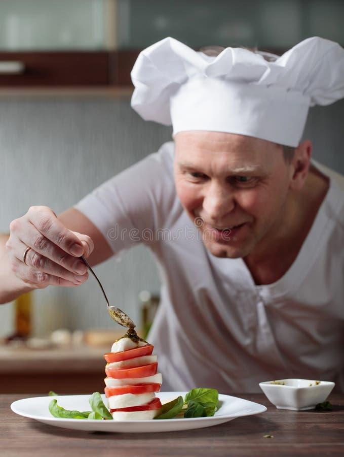 Шеф-повар подготавливает закуску с моццареллой и соусом песто стоковое фото rf
