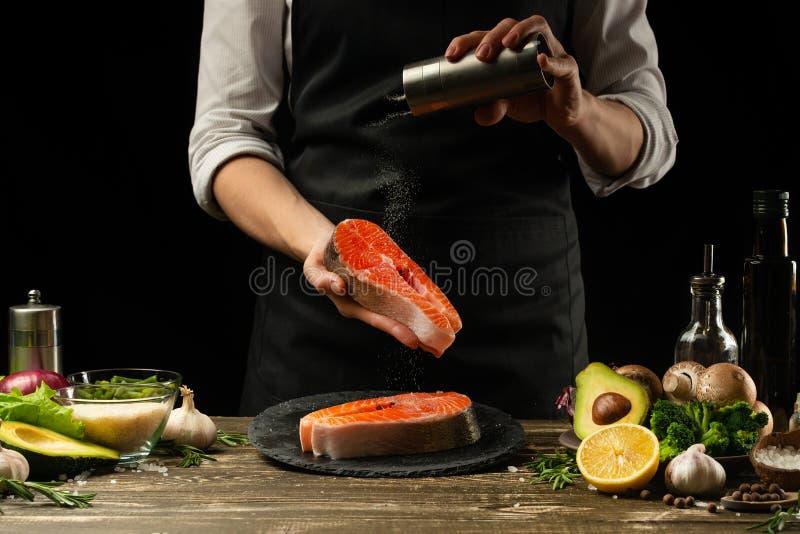 Шеф-повар подготавливает свежих рыб семг, форели Crumbu, брызгает соль моря с ингредиентами подготовлять еды рыб Salmon стейк вар стоковые фотографии rf