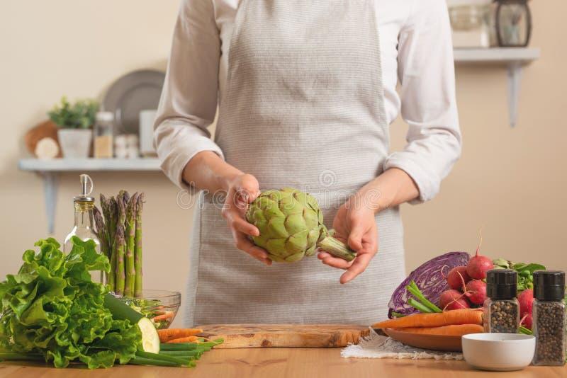 Шеф-повар подготавливая артишок Концепция теряя здоровой и полезной еды, вытрезвителя, vegan есть, диеты, варя Медленная еда, ком стоковая фотография
