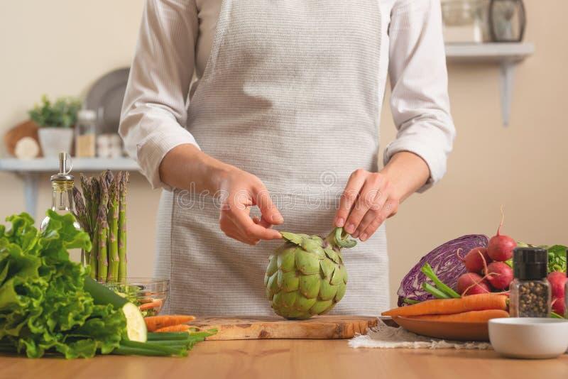 Шеф-повар подготавливая артишок Концепция теряя здоровой и полезной еды, вытрезвителя, vegan есть, диеты, варя Медленная еда, ком стоковые фото