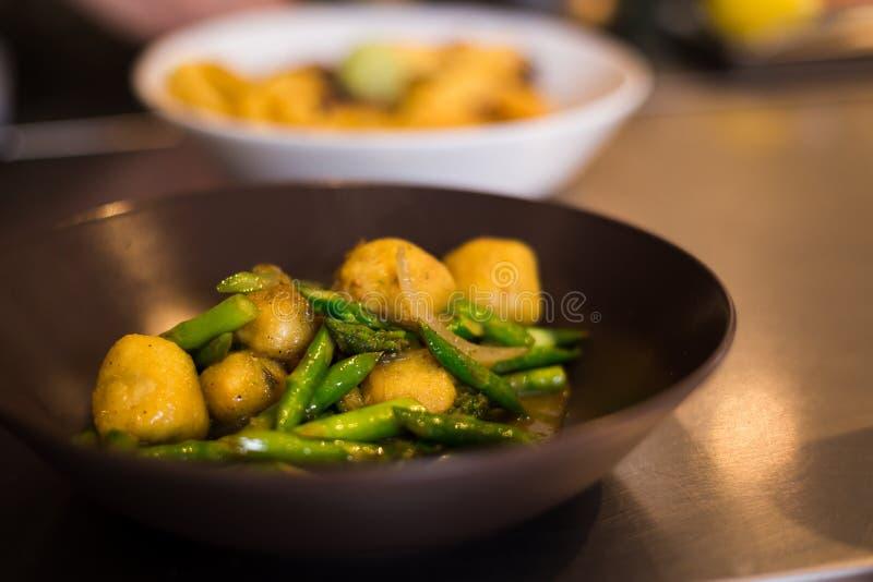 Шеф-повар покрывая свежий gnocchi рикотты в итальянском ресторане стоковые изображения rf