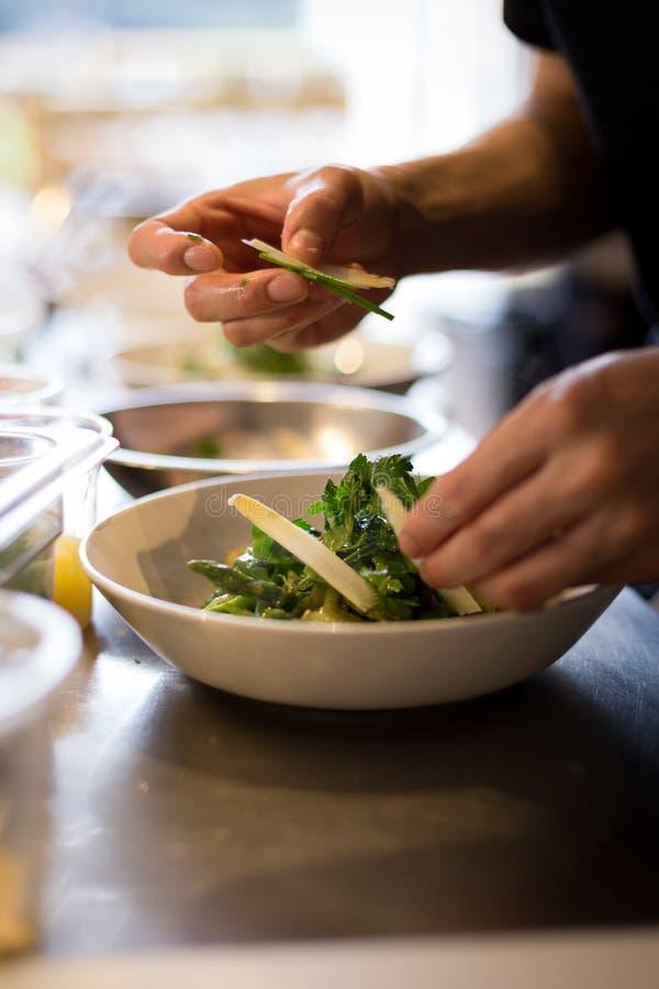 Шеф-повар покрывая свежий gnocchi рикотты в итальянском ресторане стоковое изображение