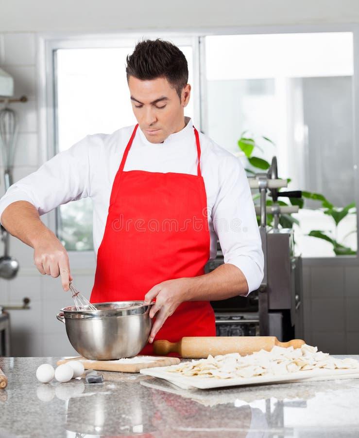 Шеф-повар подготавливая макаронные изделия равиоли в коммерчески кухне стоковое изображение rf