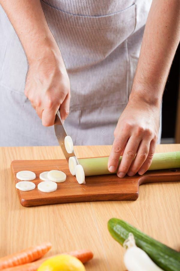 Шеф-повар прерывая лук-порей в кухне стоковые фотографии rf