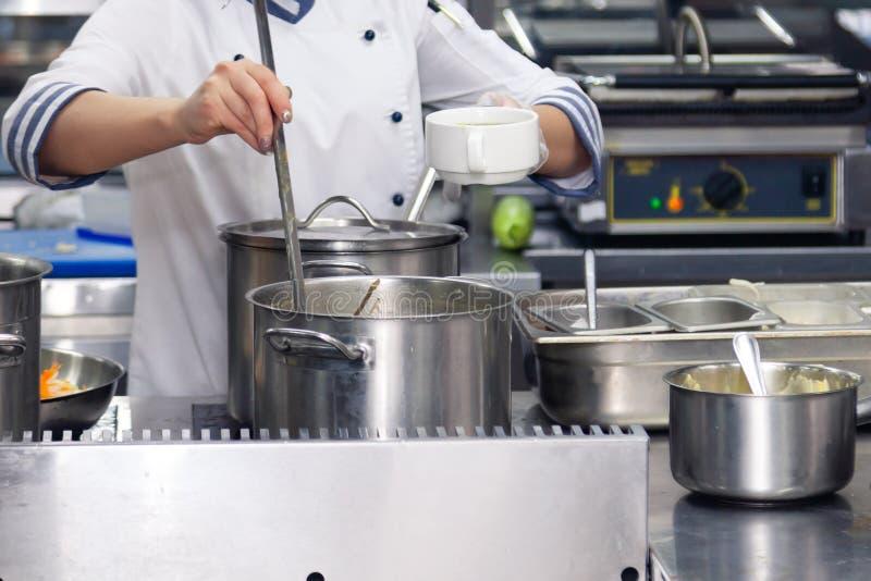Шеф-повар пробует еду Утвари кухни, плита с крышками баков металла и ветроуловители Продукты условий и срока годности при хранени стоковые фотографии rf