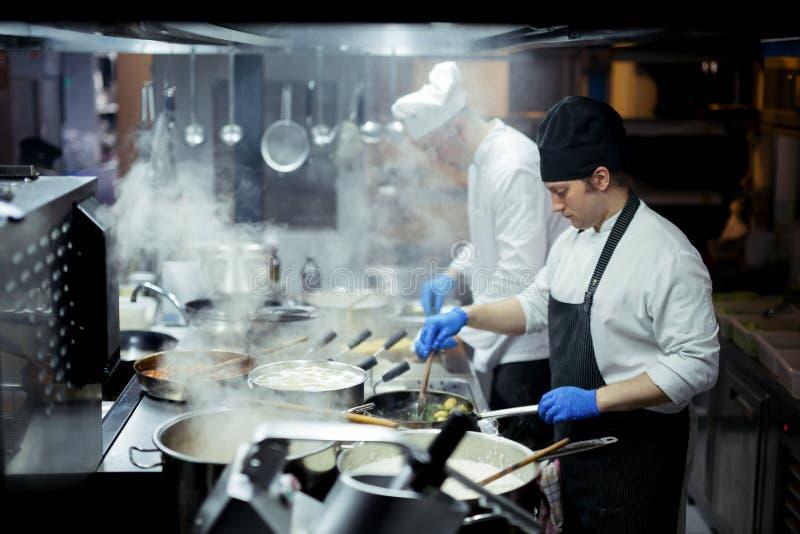 Шеф-повар работая на кухне стоковое фото rf