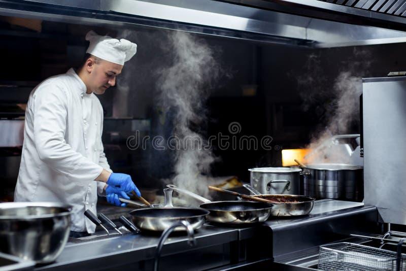 Шеф-повар работая на кухне стоковое фото