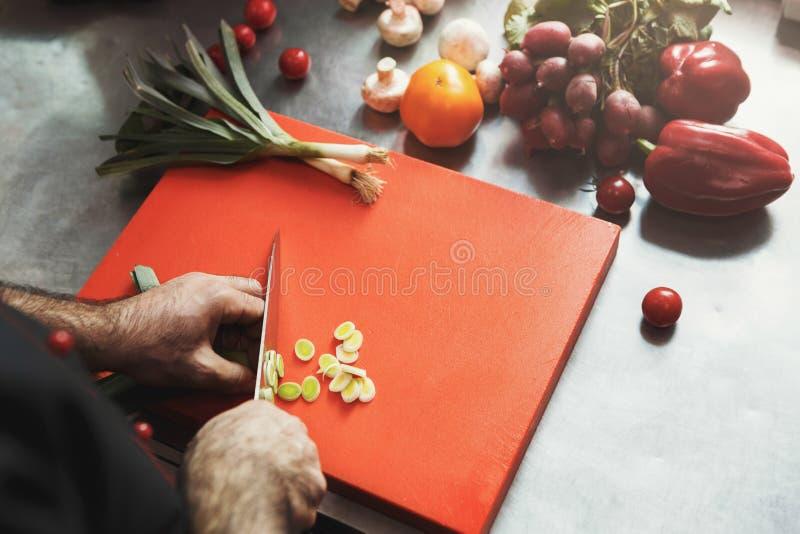 Шеф-повар режа свежие овощи для салата стоковая фотография