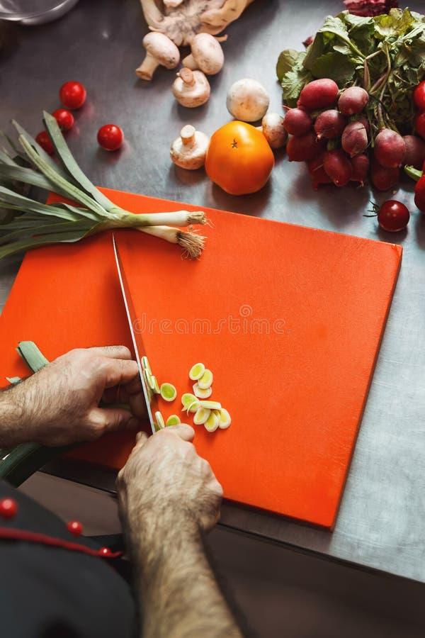 Шеф-повар режа свежие овощи для салата стоковое изображение rf