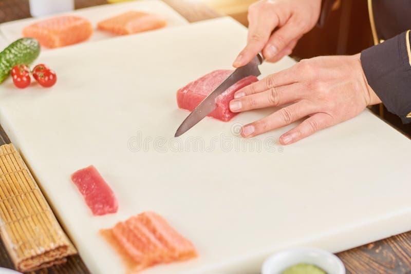 Шеф-повар режа сырцовый тунца на разделочной доске стоковое фото