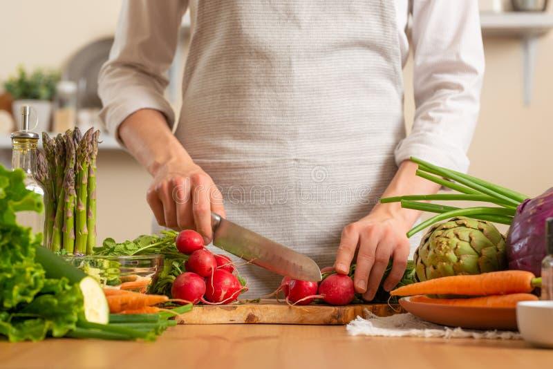 Шеф-повар режет свежую редиску для салата Концепция теряя здоровой и полезной еды, вытрезвителя, vegan есть, диеты, варя Медленна стоковые фото