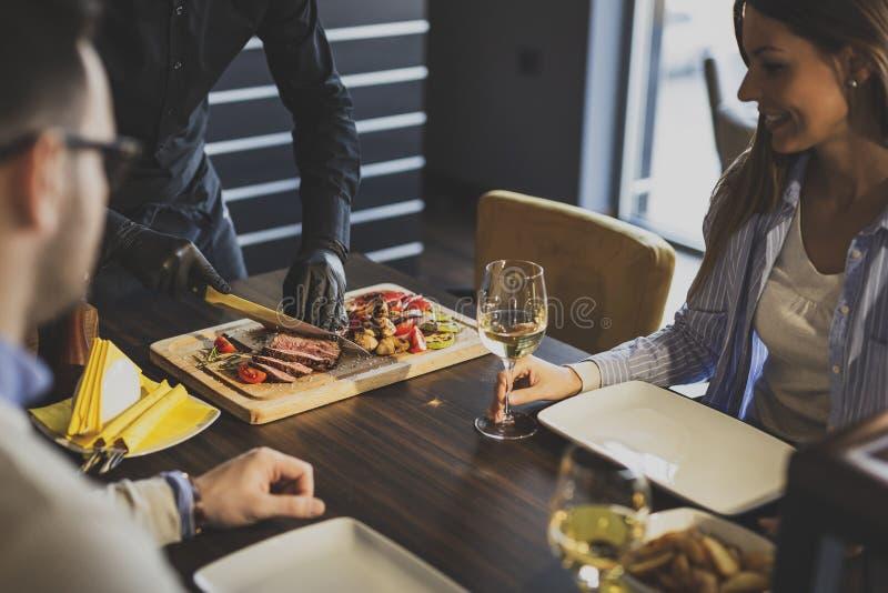 Шеф-повар ресторана отрезая стейк стоковое фото