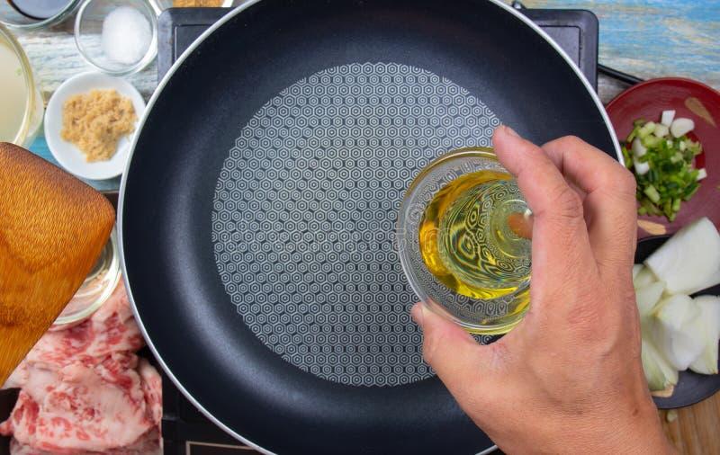 Шеф-повар сосредоточенно изучая масло для того чтобы приготовить для варить стоковые фото