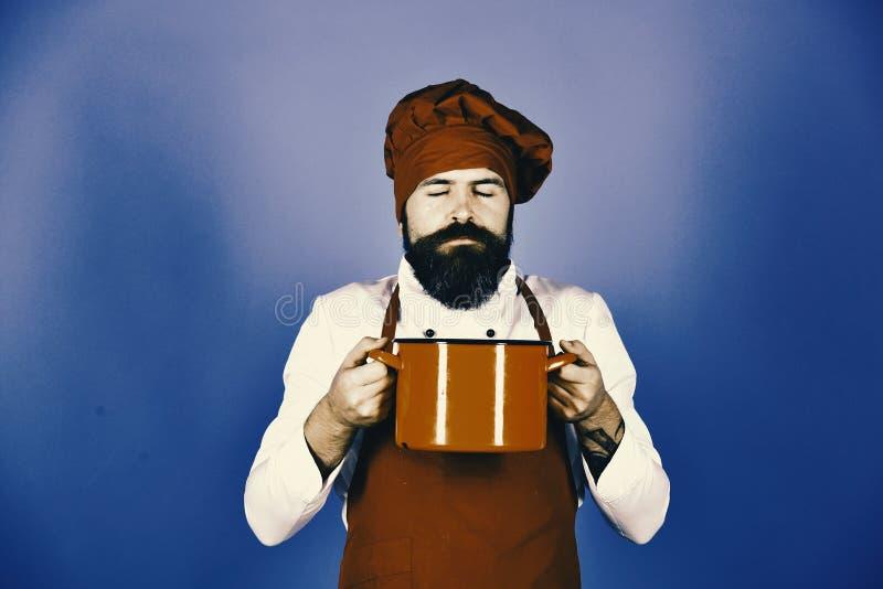Шеф-повар с красными сотейником или кастрюлькой Человек с бородой держит kitchenware на голубой предпосылке стоковая фотография rf